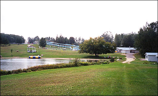 View of a resort and waterslides with a lake in foreground.