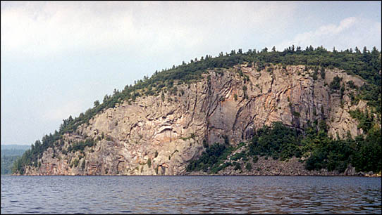 A landscape of a big stone cliff at the edge of a lake.