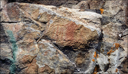 A faded pictograph painted on a rock.