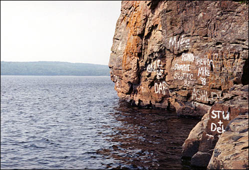 A view of the rock emerging from the water with grafiti painted on it.