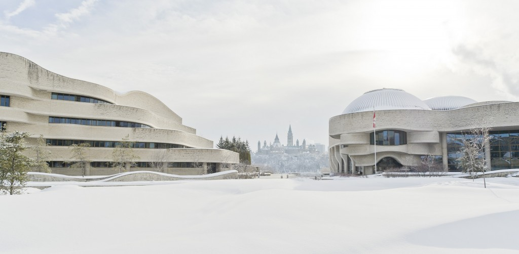 A photograph of the Canadian Museum of History and the Curatorial Building in the winter, with the Parliament buildings in the background