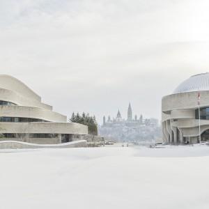 Photographie du Musée canadien de l'histoire et du pavillon administratif en hiver, avec les édifices du Parlement en arrière-plan.