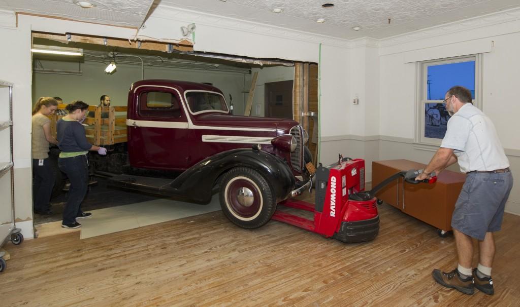 Des experts des collections sortent la camionnette Dodge Fargo de la salle du Canada en suivant le trajet modifié.