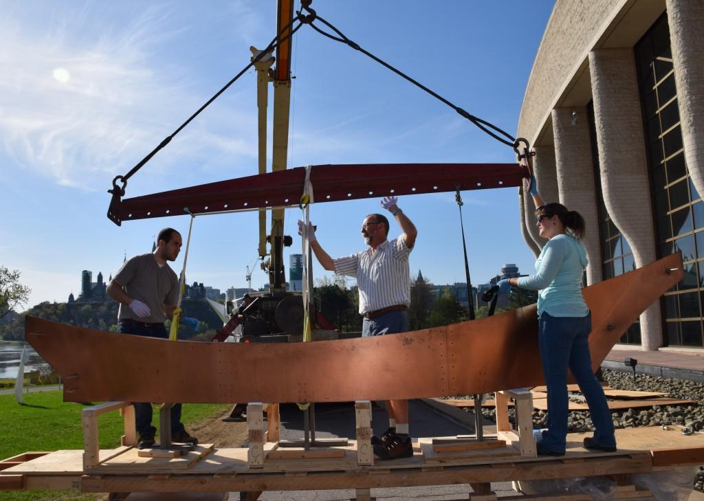 On s'apprête à réinstaller le canot sur la base de la sculpture.