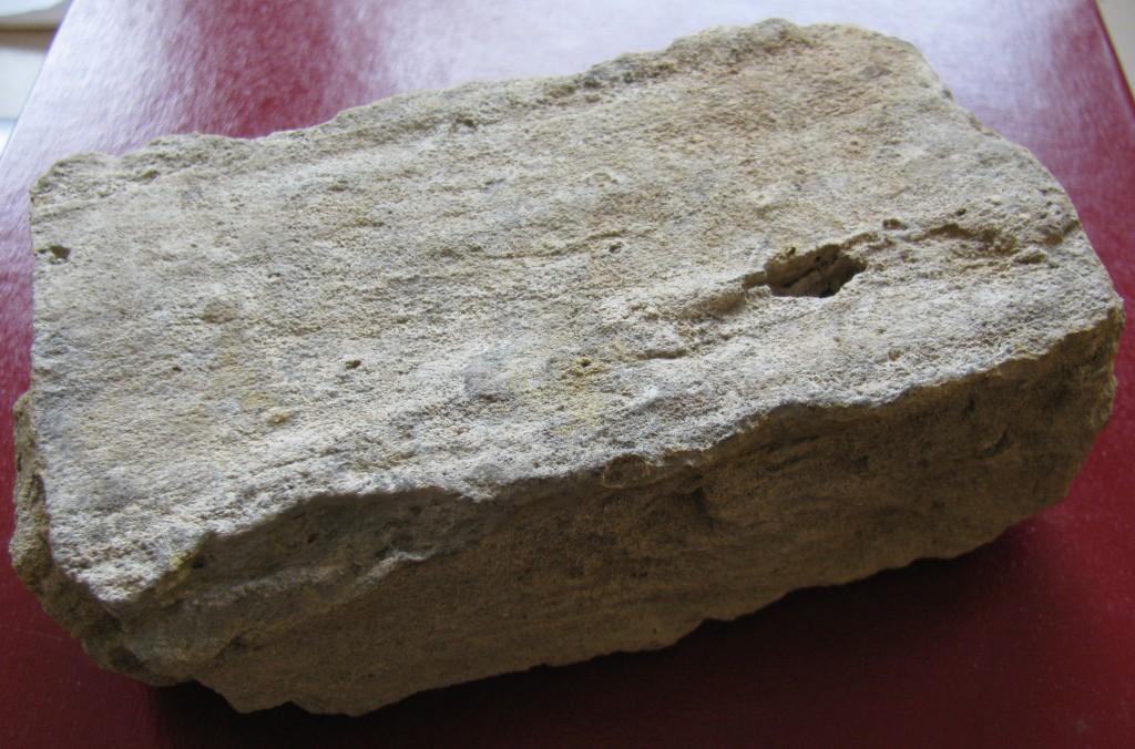 Légende : Cette brique « flamande » a été trouvée alors qu'elle allait disparaître dans les eaux de la rivière Severn, en 2015. Elle fait partie des vestiges archéologiques d'un poste de la Compagnie de la Baie d'Hudson (HBC) bâti au milieu des années 1700 à Fort Severn. Elle a sans doute été récupérée d'un poste plus ancien de la HBC, situé à plusieurs kilomètres en amont.