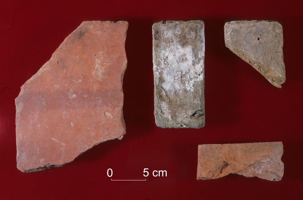 Des échantillons de briques issues de fouilles archéologiques trouvées près de l'ancien fort, en amont de Fort Severn : une tuile rouge à gauche, deux briques « flamandes » à droite et un fragment de brique rouge « anglaise » en bas à droite.