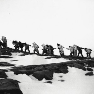 Inuit campers hauling a small boat at Keatuk camp, Baffin Island