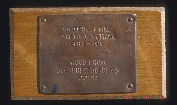 Morceau de bois provenant de la porte du bureau de sir Robert Borden dans la première Chambre des communes. La petite plaque de cuivre porte la mention suivante : « SOUVENIR OF FIRE PARL'T BLDG'S OTTAWA FEB. 3 – 1916. WOOD FROM SIR ROBERT BORDEN'S DOOR. » (Souvenir de l'incendie des édifices du Parlement survenu le 3 février 2016 à Ottawa – bois de la porte du bureau de sir Robert Borden), Musée canadien de l'histoire, 7255-3242-2567-057
