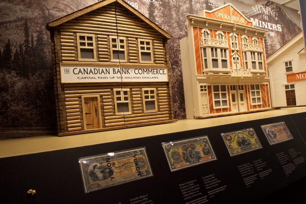 Quatre reproductions d'immeubles derrière un rail, des batées de prospecteur et des boutons sont tout ce que voit le visiteur au premier abord, en s'approchant de la vitrine. Photo : Musée de la Banque du Canada