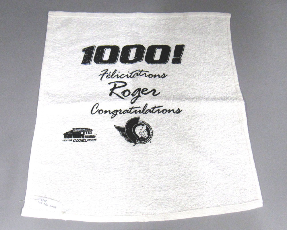 Roger Neilson inspired Vancouver's towel-waving ritual. Neilson finished his career as assistant coach of the Ottawa Senators. The team made him interim head coach for the final two games of the 2002 NHL season, so he could reach the 1,000-game mark as a head coach. They issued these towels to mark the occasion. Neilson died in 2003. Towel on loan from the Peterborough & District Sports Hall of Fame. Photo: Canadian Museum of History.