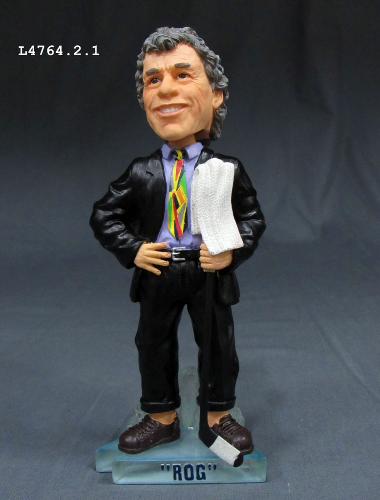 "Coach Roger Neilson was known for his innovations, and also for his wild neckties. This bobble-head doll shows ""Rog,"" with towel, and a colourful example. Doll on loan from the Peterborough & District Sports Hall of Fame. Photo: Canadian Museum of History."