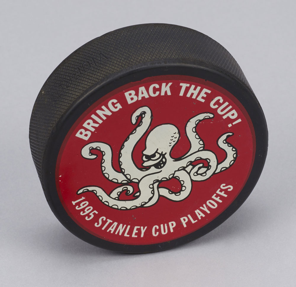 """John Finley, former team doctor for the Detroit Red Wings, kept this Viceroy Rubber puck from the 1995 playoffs. The team did not """"bring back the cup"""" that year, losing to the New Jersey Devils in the Stanley Cup Finals. Photo: Canadian Museum of History."""