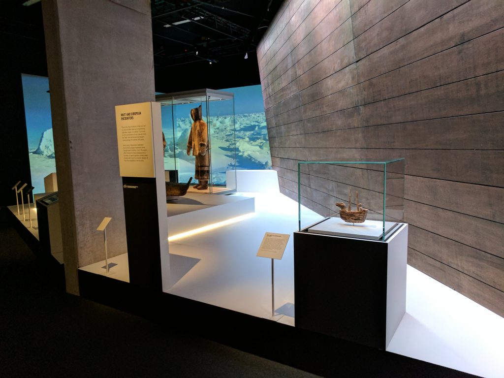 The introductory area of Death in the Ice at the National Maritime Museum includes an Inuit carving of a European ship (foreground). Photo: Canadian Museum of History.