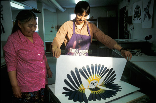 Kenojuak Ashevak and Kavavaow Mannomee in the process of creating the print The Sun's Return, created by the stonecut and stencil technique
