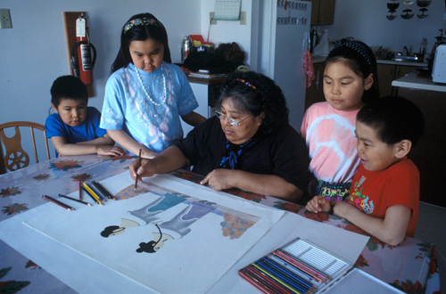 Pitaloosie Saila, surrounded by children, using coloured pencils to draw what would become a print depicting two women