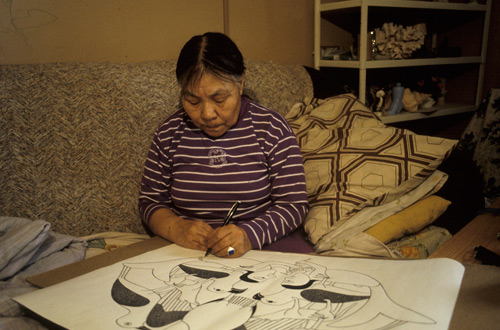 "Kenojuak Ashevak using a black ink felt pen to draw what would become the print ""Guardians of the Owl"""