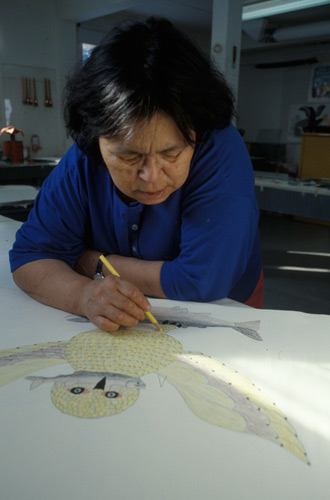 Qaunak Mikkigak using coloured pencils to draw a snowy owl with a fish in its beak and a second fish in its talons