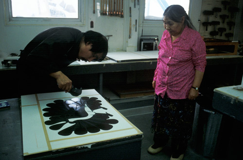 Kenojuak Ashevak and Qiatsuq Niviaqsi in the process of creating the print 'Audacious Owl', created by the stonecut and stencil technique