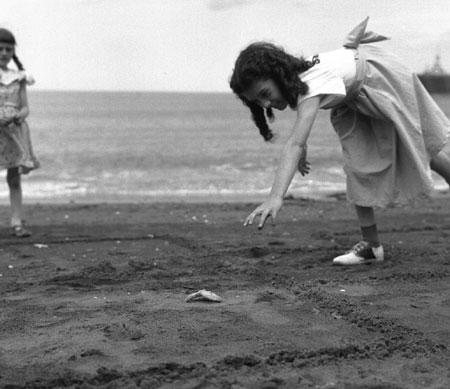 Yvette Larivée, 10 ans, jouant à la marelle avec une étoile de mer sur la plage de Grande Vallée, Gaspésie, Québec, 1958., © MCC/CMC, Carmen Roy, J15080