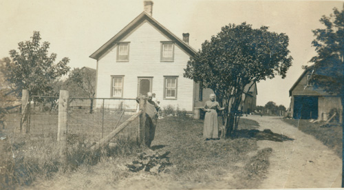 Photograph of Mr. and Mrs. Hawn, weavers, standing in front of their house in Newington, Ontarioo