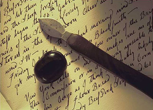 Picture of an agate stone and an ink eraser on yellowed paper.