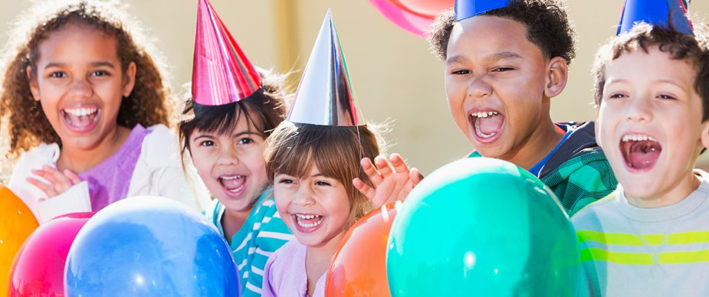 Children celebrating with hats and balloons