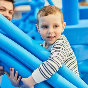 Child with big blue foam blocks