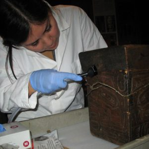 A woman cleans a bentwood box.