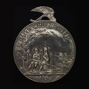 """Circular medal featuring two figures sitting side by side, with the words """"Happy while united"""" and the year 1764."""