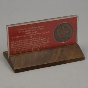 Red plaque on a wooden stand, with an inset wooden medallion showing a map of Canada's East Coast