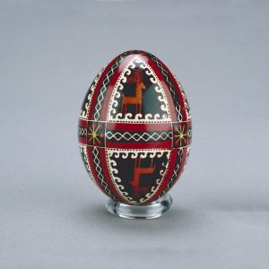 A Ukrainian Easter egg decorated with mirror images of deer, divided by intricate spiral and ribbon shapes, intersected by flowers.