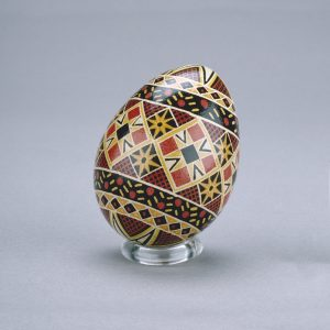 A Ukrainian Easter egg decorated with an intricate star-and-diamond pattern in black, red, brown and white.