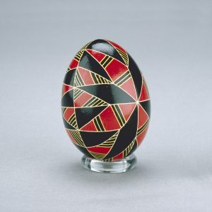 A Ukrainian Easter egg decorated with contrasting diamond shapes in red and black, separated by yellow lines.