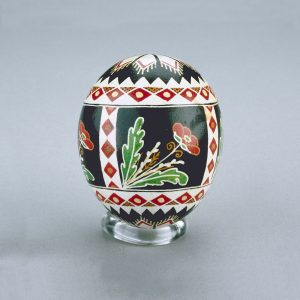A Ukrainian Easter egg decorated with diamond and triangle shapes in red, white, black and yellow, with poppy motifs.