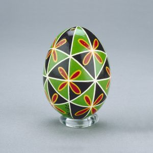 A Ukrainian Easter egg decorated with a green-and-black triangle pattern, intersected by vibrant red-and-yellow flowers.