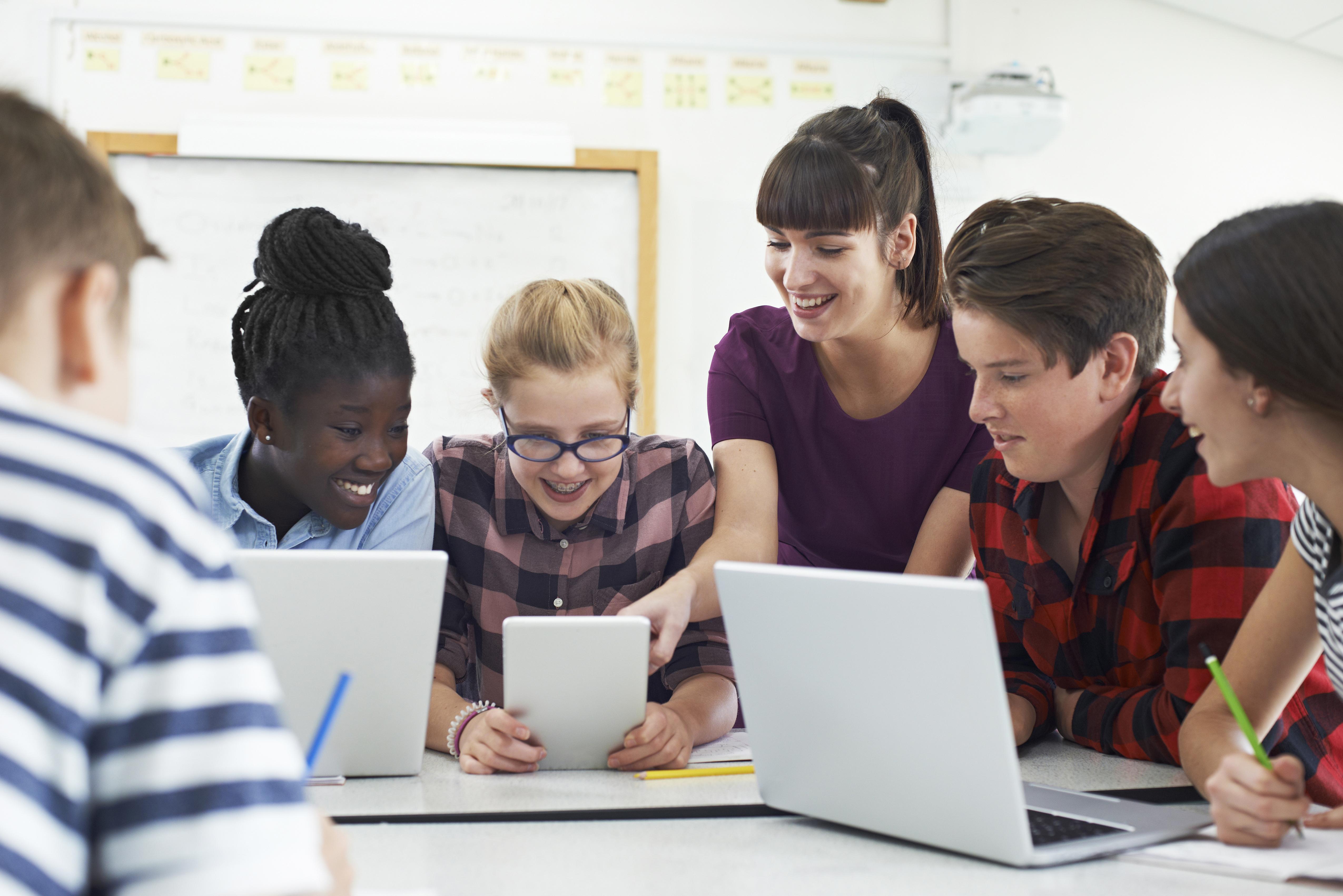 Des élèves travaillant sur des ordinateurs portables pendant que l'enseignante montre quelque chose sur un écran.