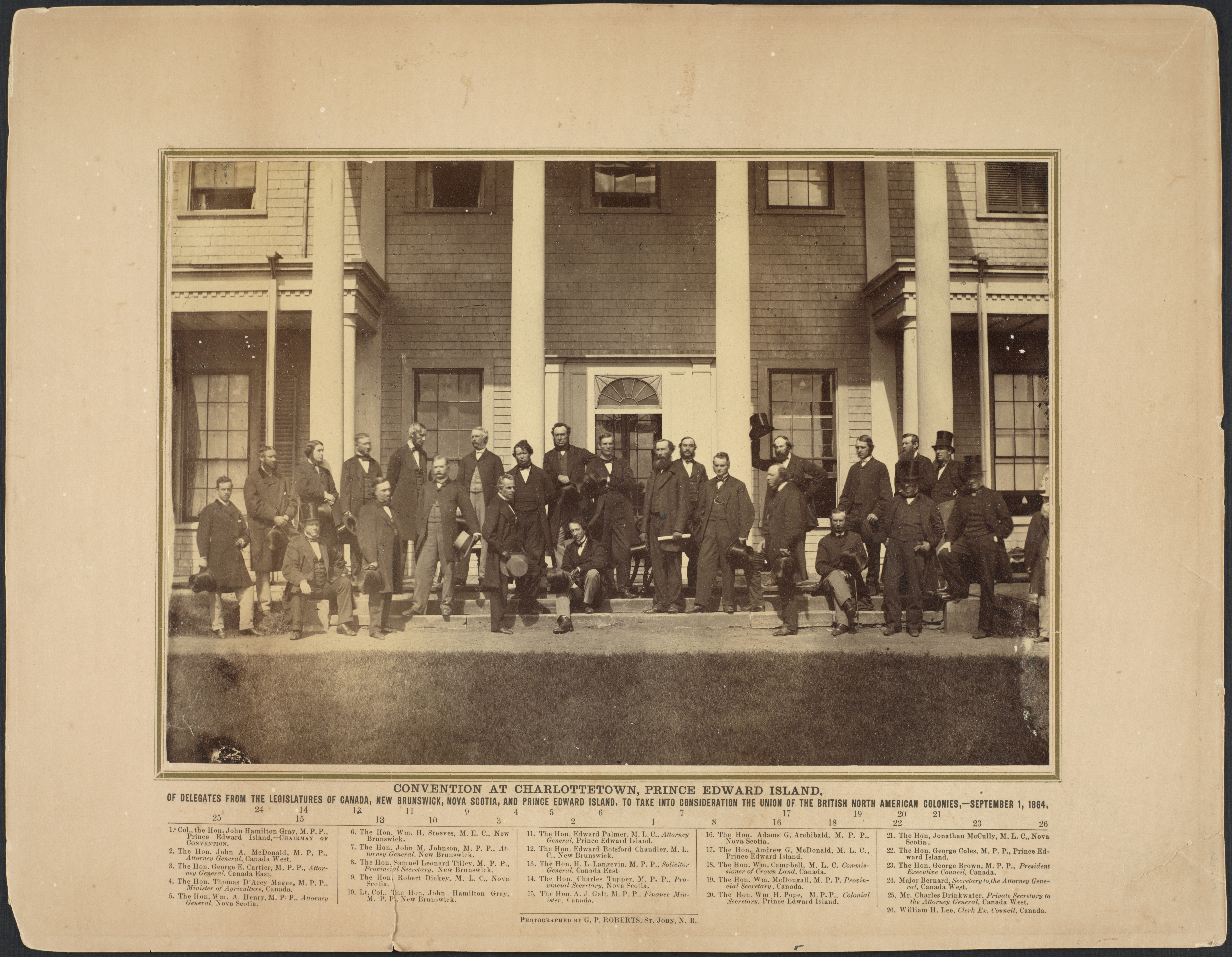 Black and white photo of men gathered in front of a building.