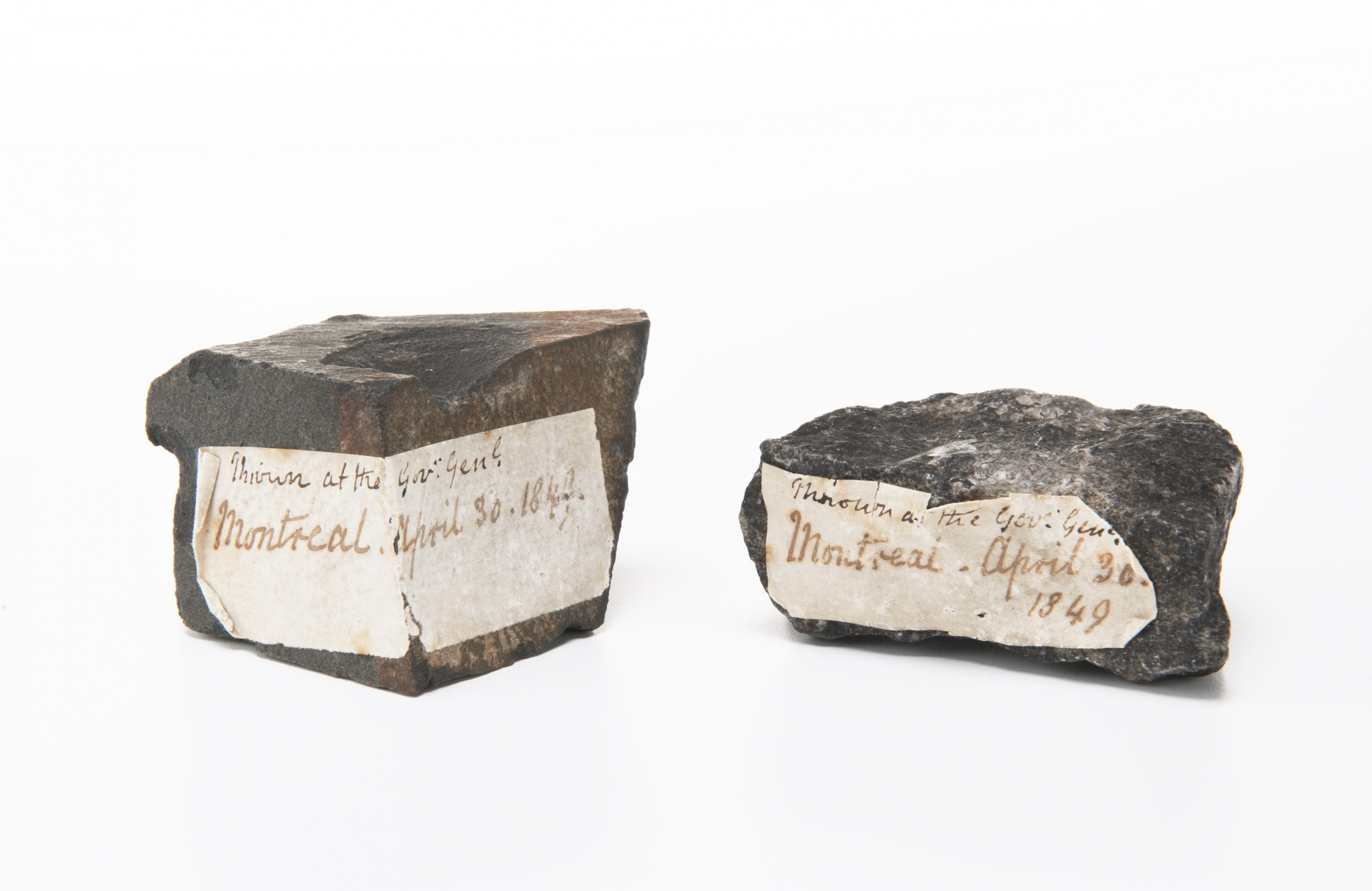 two rocks with dated labels on them.
